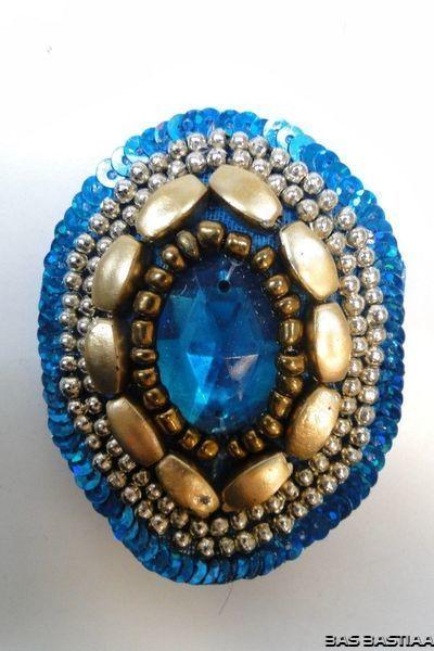 Applicatie met steen en kralen ovaal blauw goud